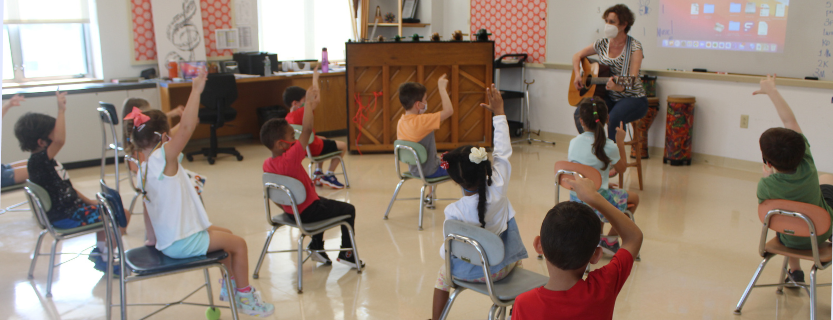 Students clap and do hand motions along with music teacher Melissa Richardson.