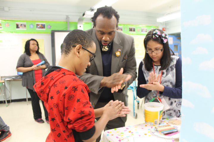 Dr. Jude Arthur participating in the STEM fair at MS 72 with students.