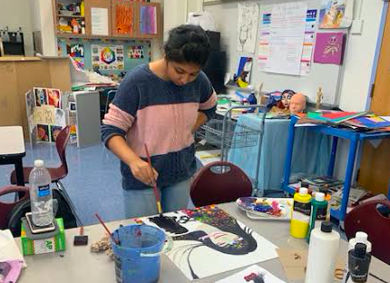 Student painting a self-portrait in art club