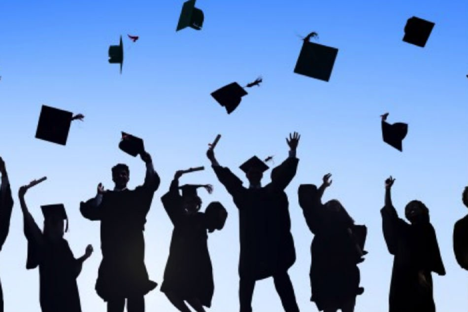 Graduates jumping and removing their caps