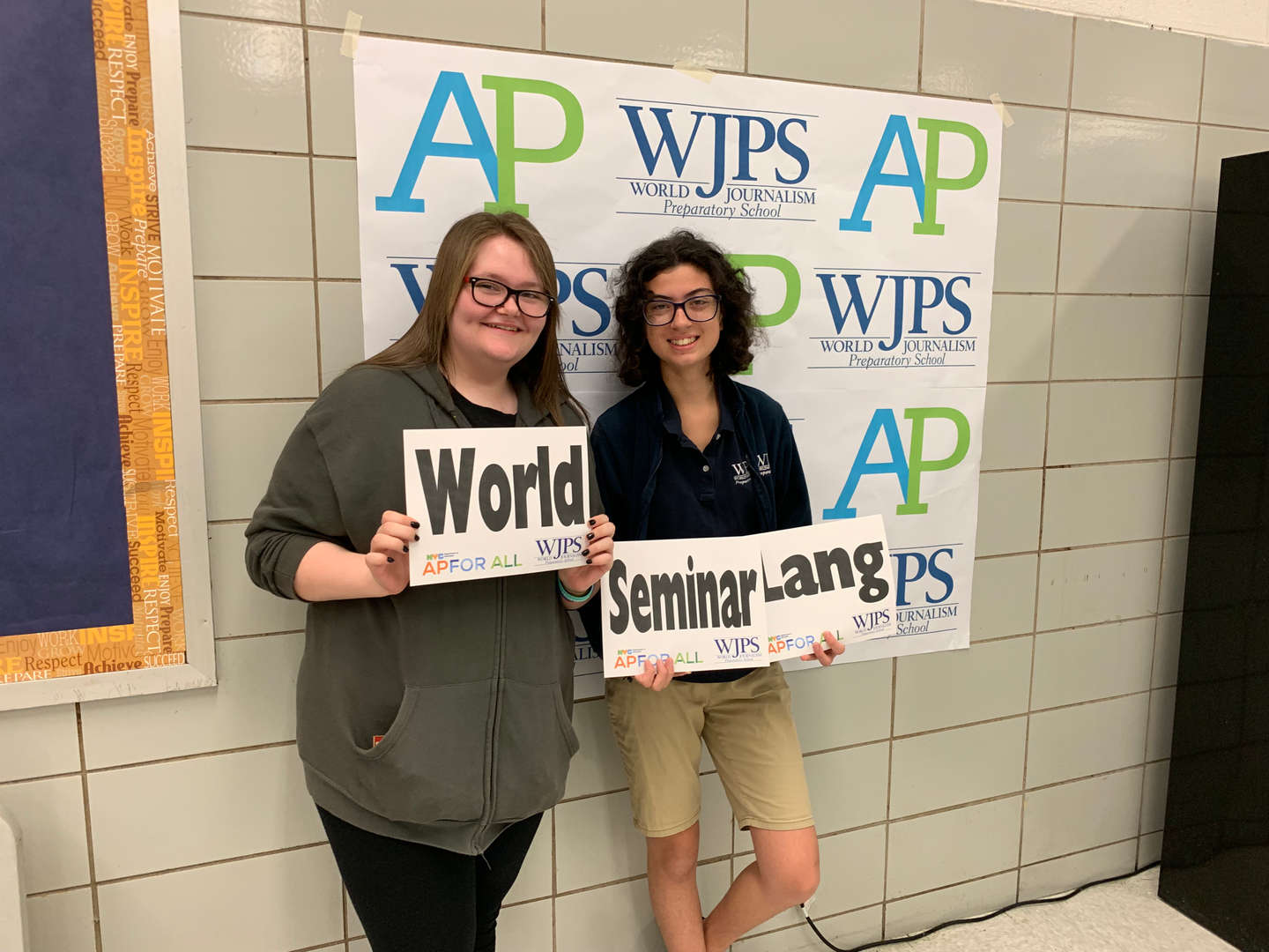 two female students holding ap subject signs