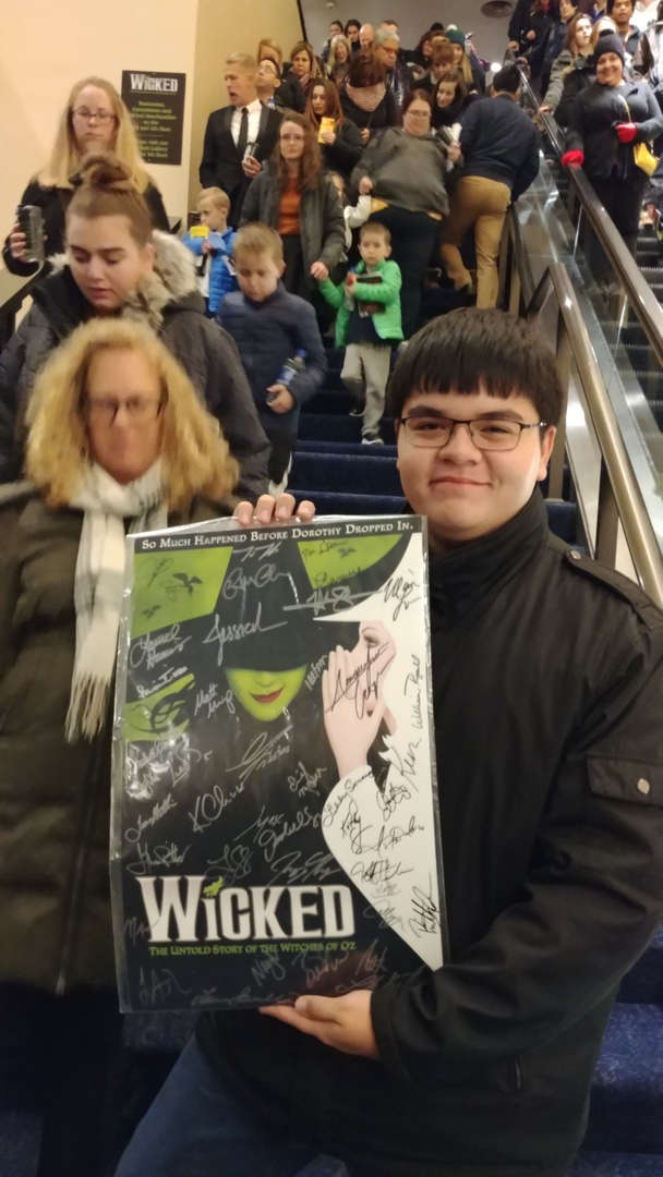 male student holding Wicked Poster