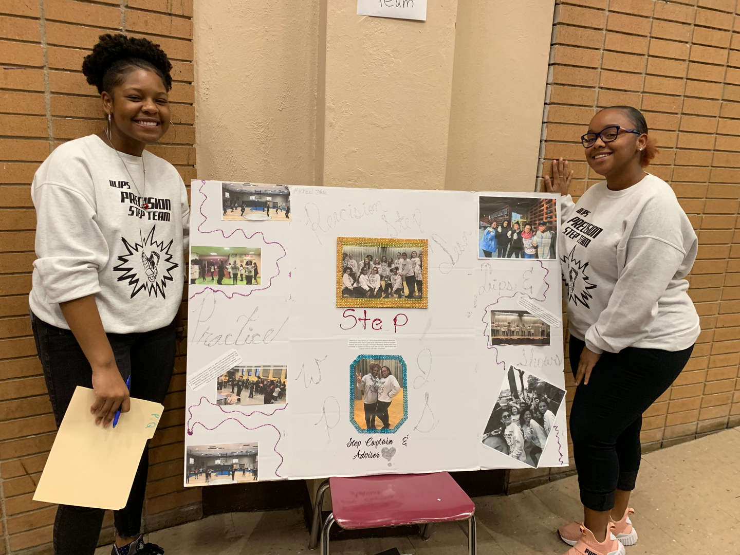 two students with club poster