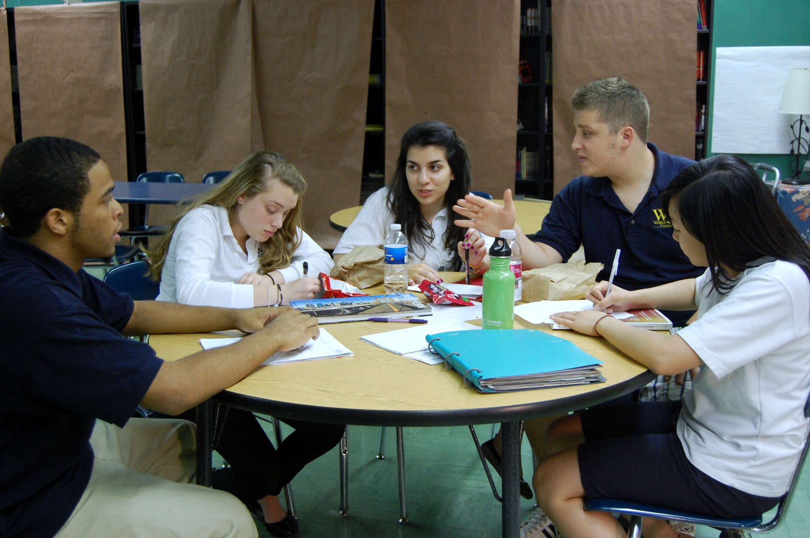 six students sitting at a round table studying