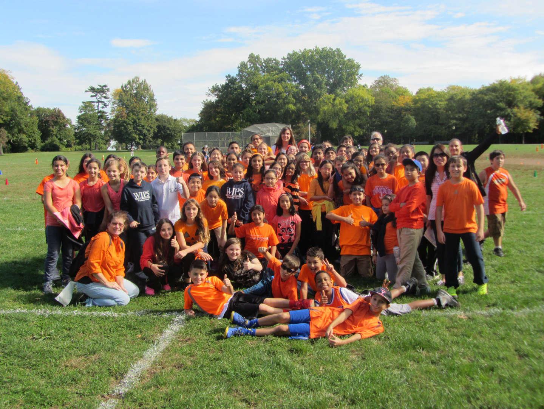 students in field wearing orange shirts