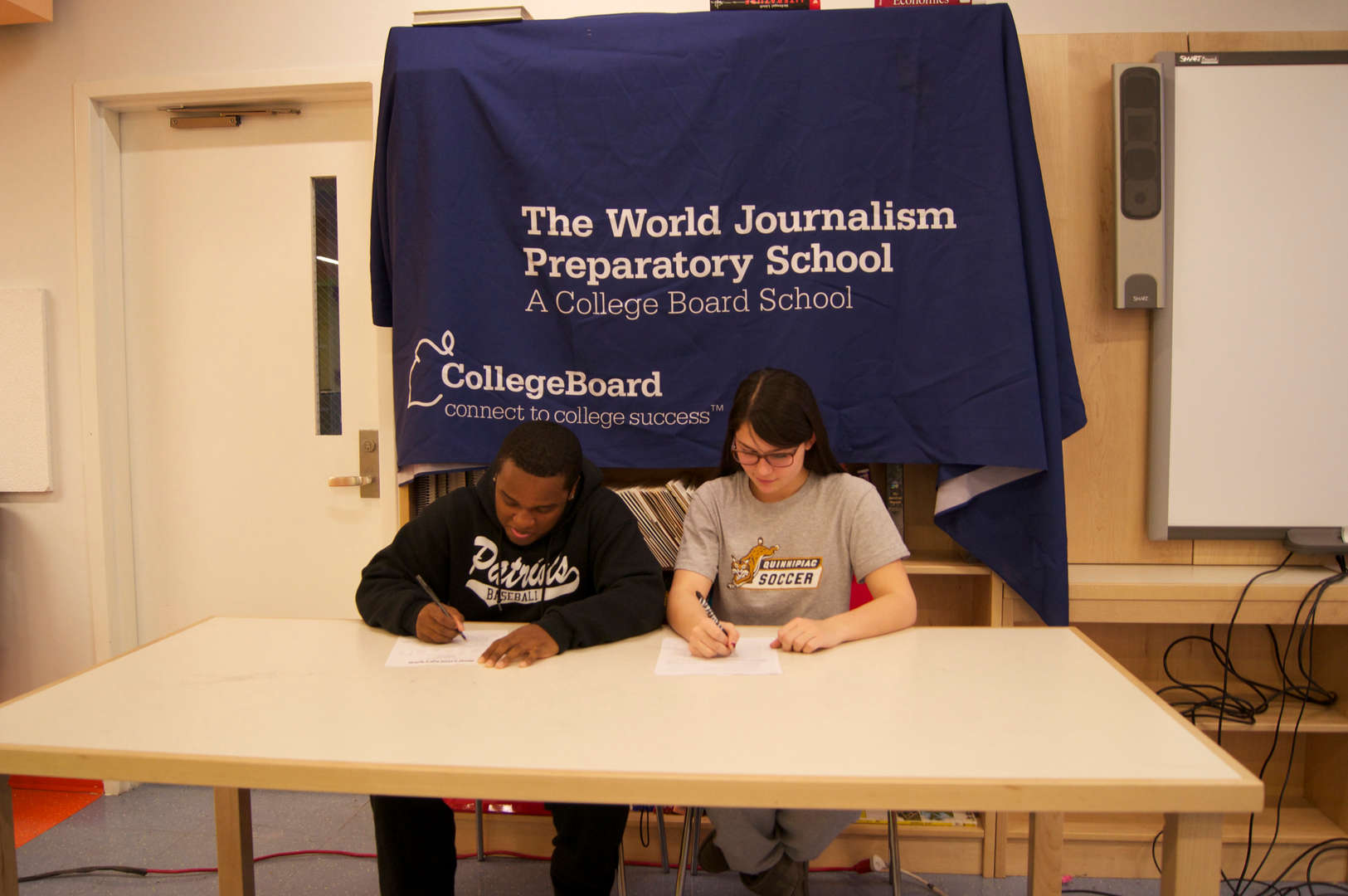 two students signing sports applications