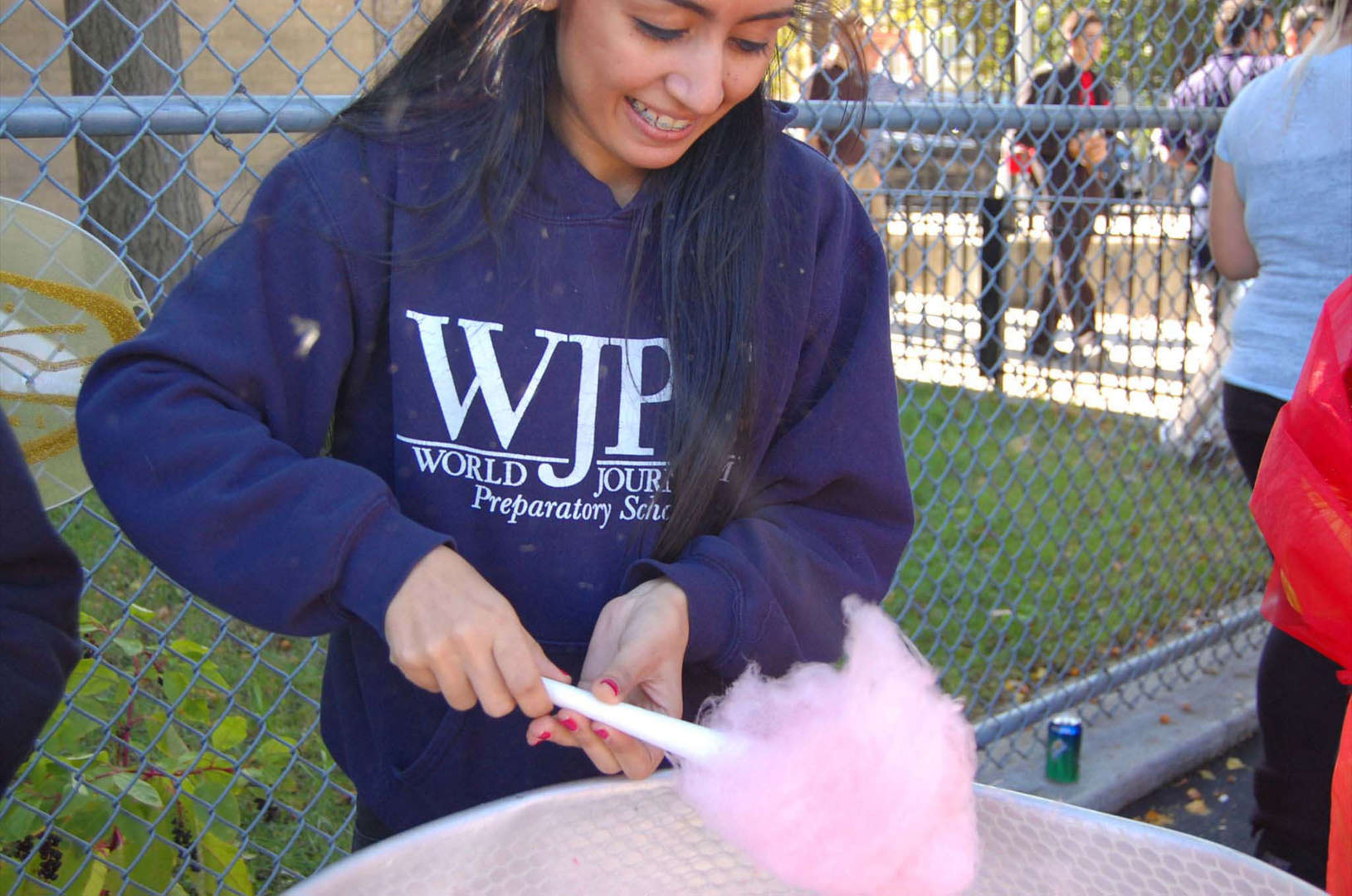 girl in blue sweatshirt making pink cotton candy