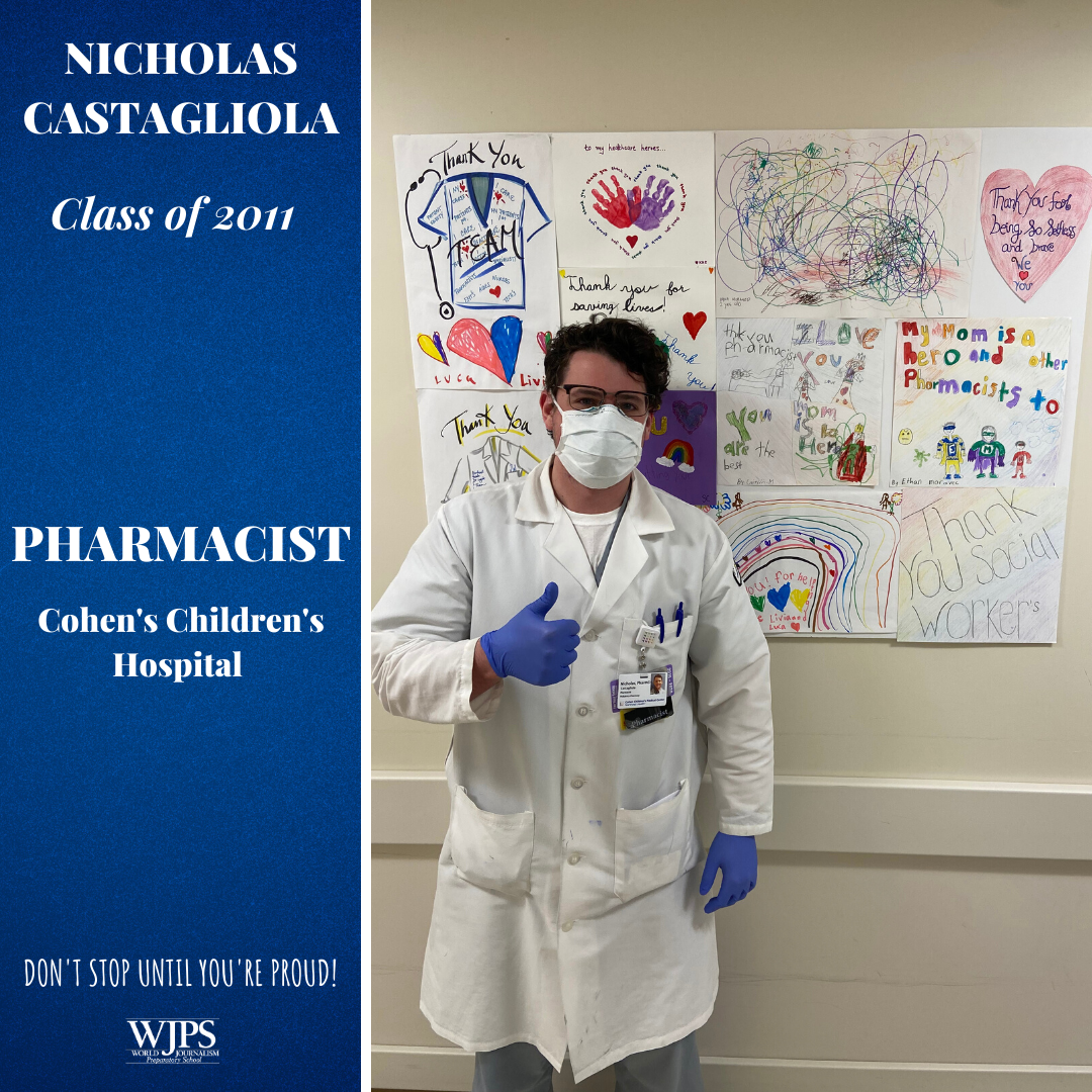male pharmacist in lab coat and mask in front of wall of children's drawings