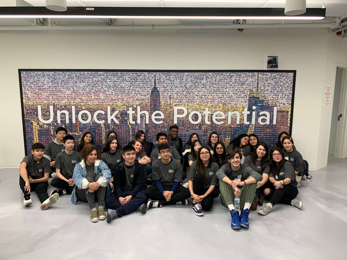 students in front of picture of skyline