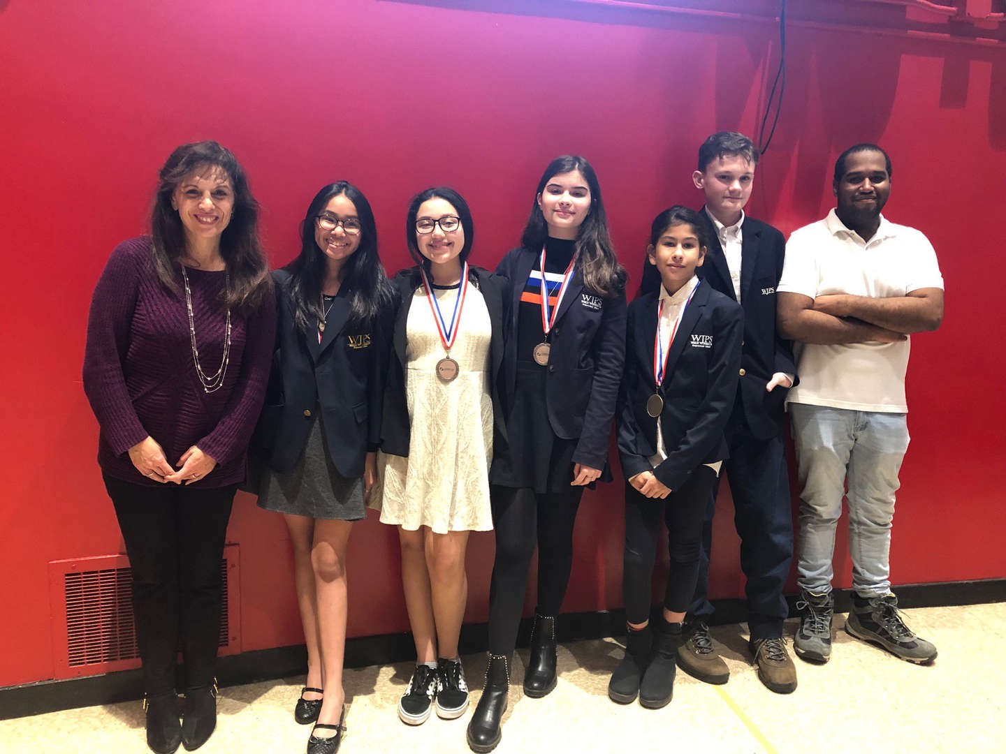 group of students with debate team medals