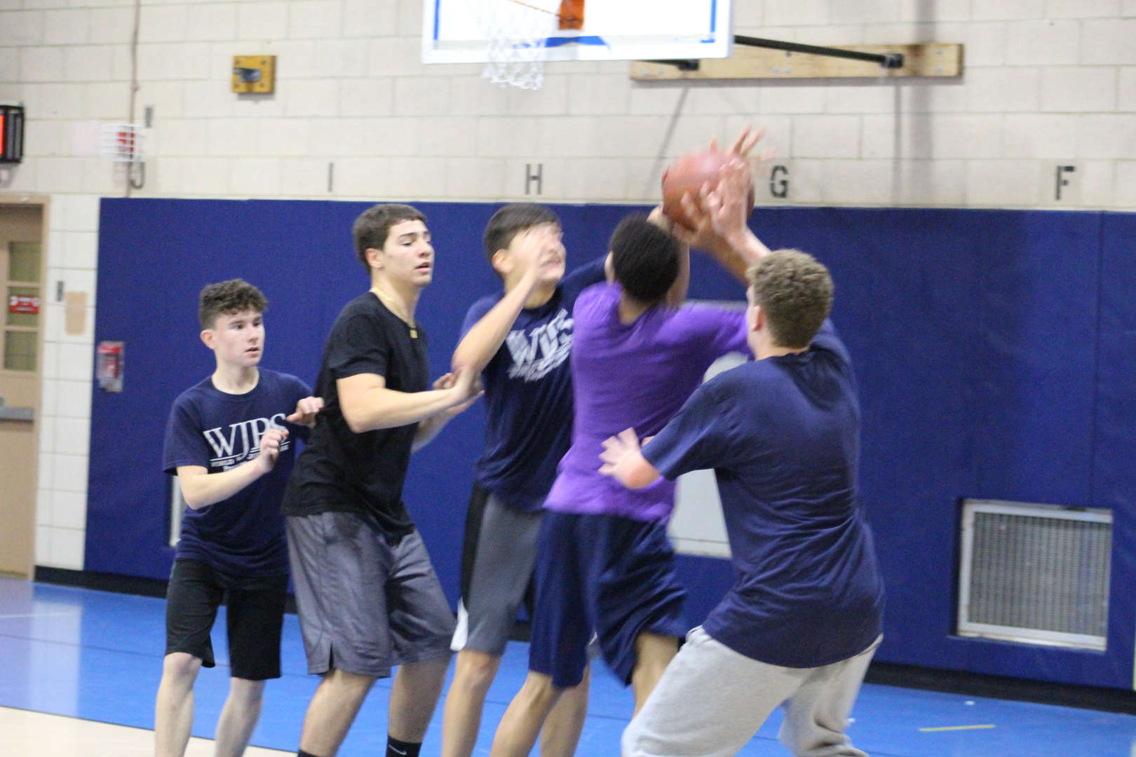group of students running up to basketball hoop