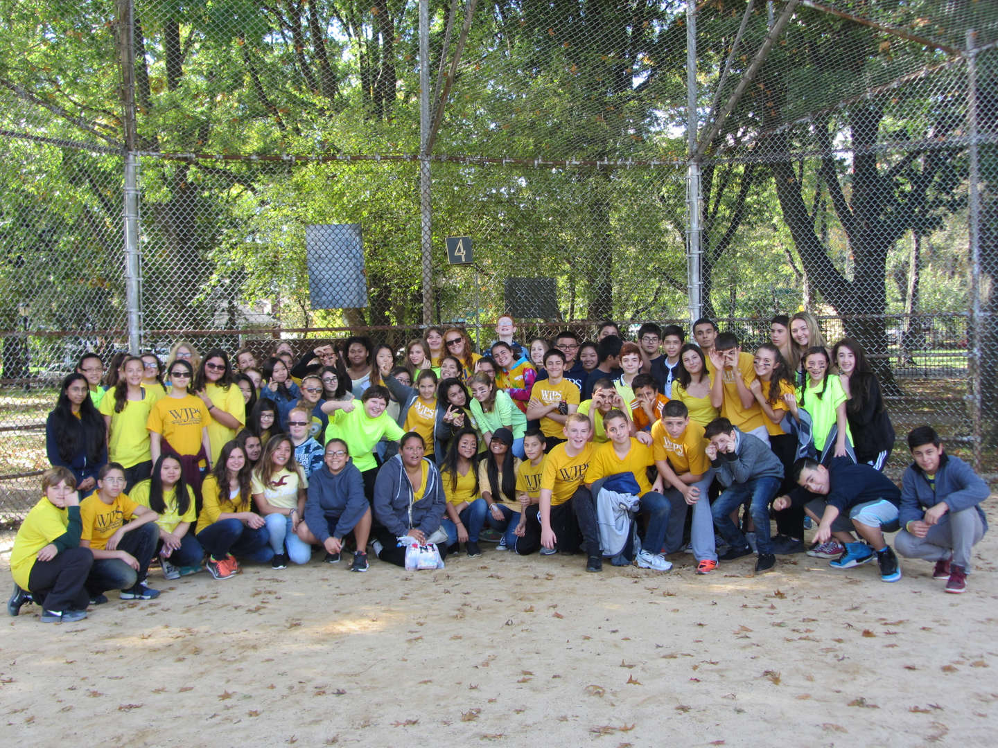 group of students posing in yellow tee shirts for field day