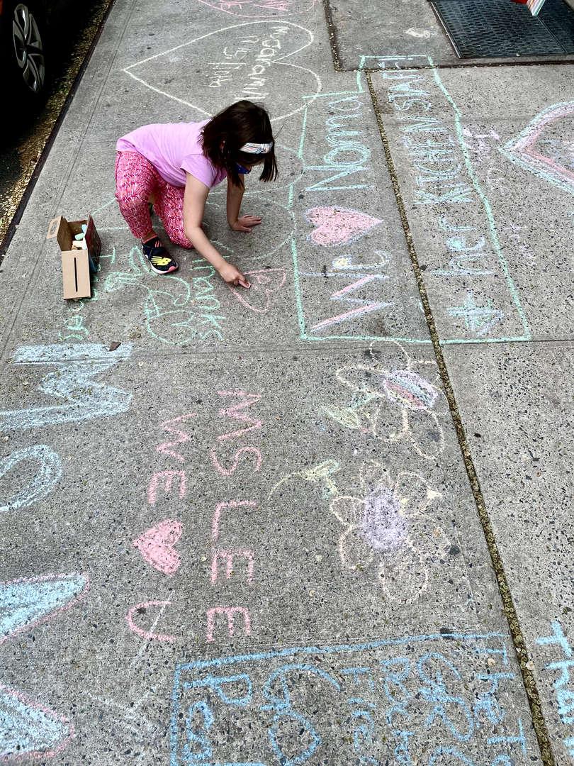 child chalking sidewalk
