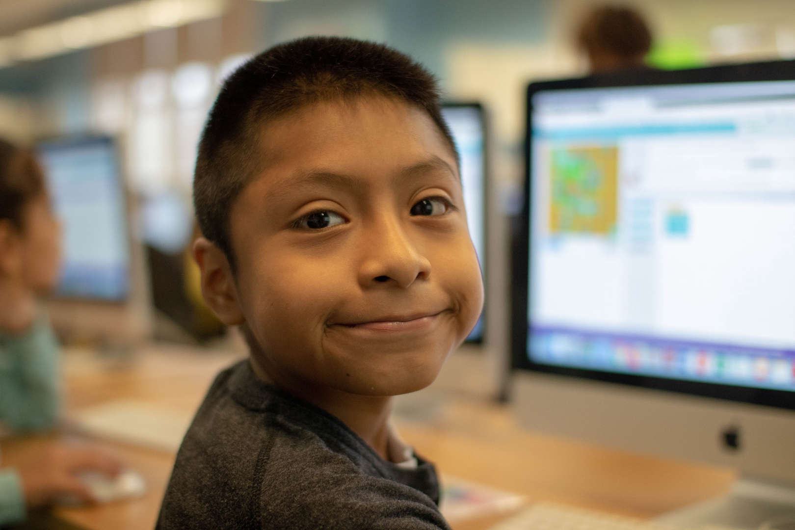Boy Sitting at Computer, turning around to smile
