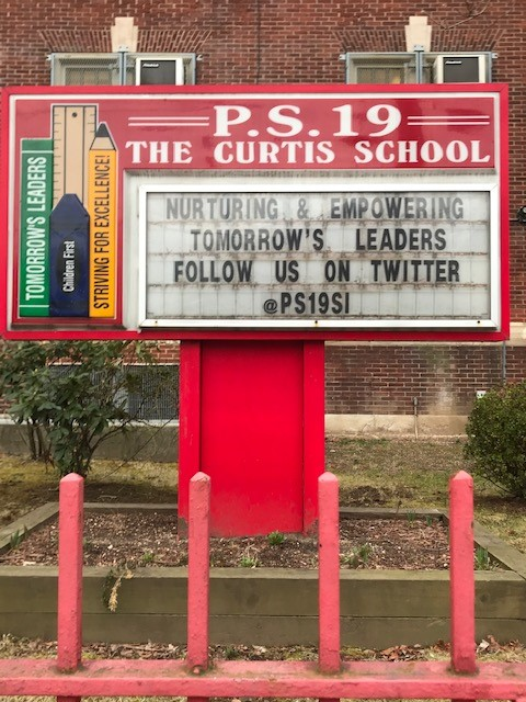PS19 outdoor sign. Nurturing and Empowering Tomorrow's Leaders. Follow us on Twitter @PS19SI