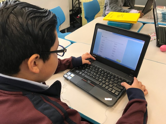 A student practicing multiplication facts on a computer.