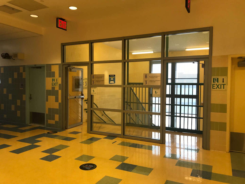 3rd floor stairway exit facing large windows.