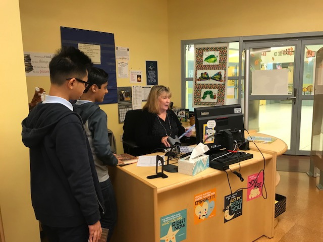 Students checking out books with the librarian.