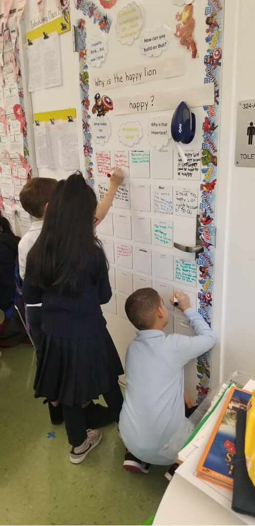 Students writing on the dry-erase board.