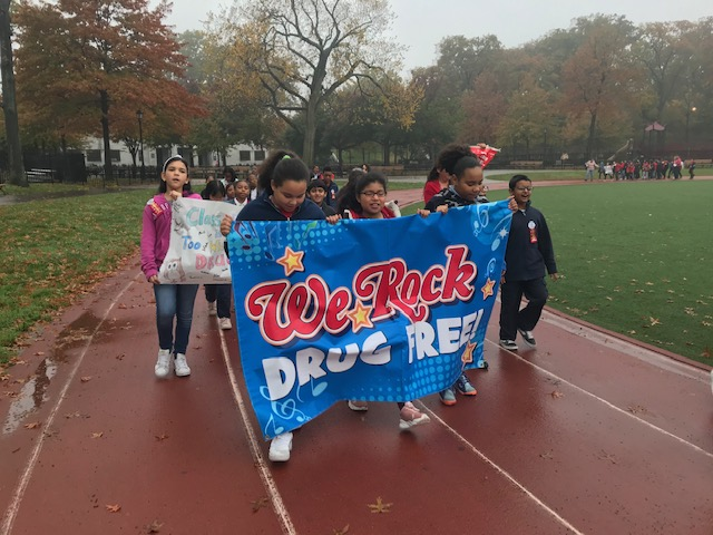 "Students march holding a banner, ""We Rock, Drug Free."""