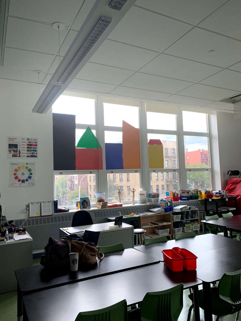 PS 56 art room facing large windows with students work.