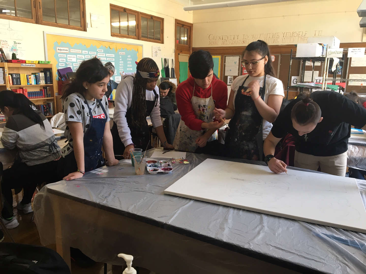 Five students creating a piece of artwork