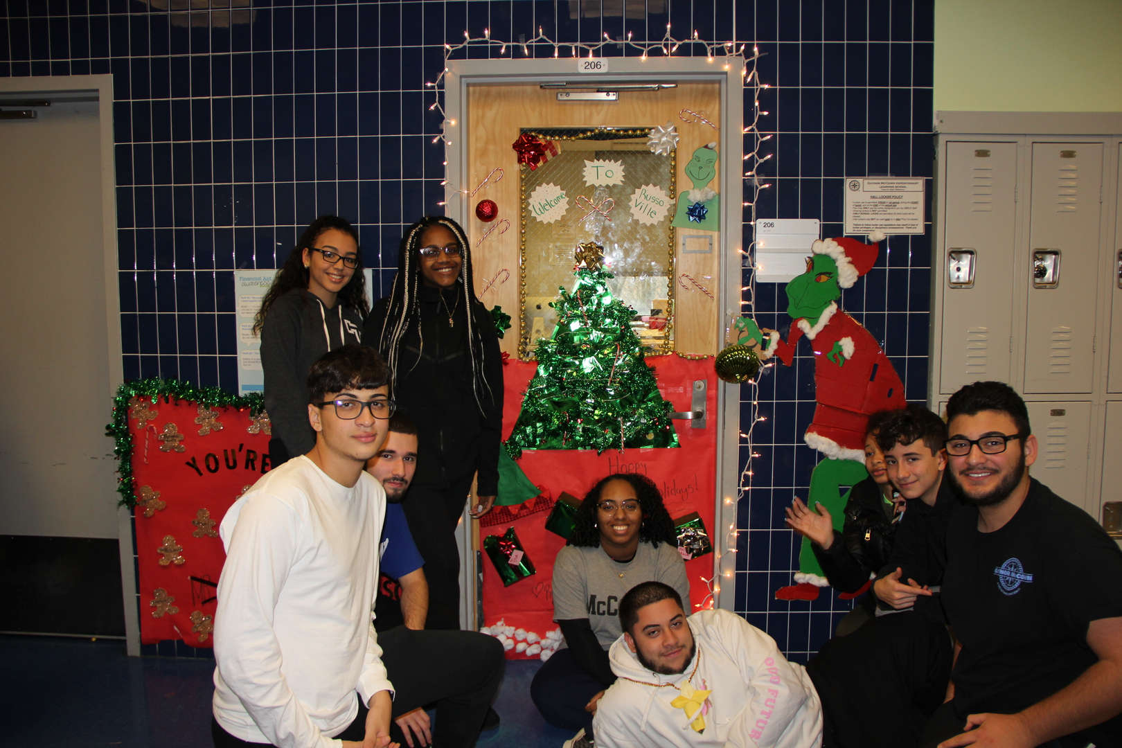 Group of students pose in front of Christmas tree door decor