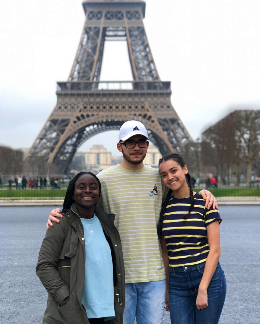 Three students posing in front of the Eiffel Tower