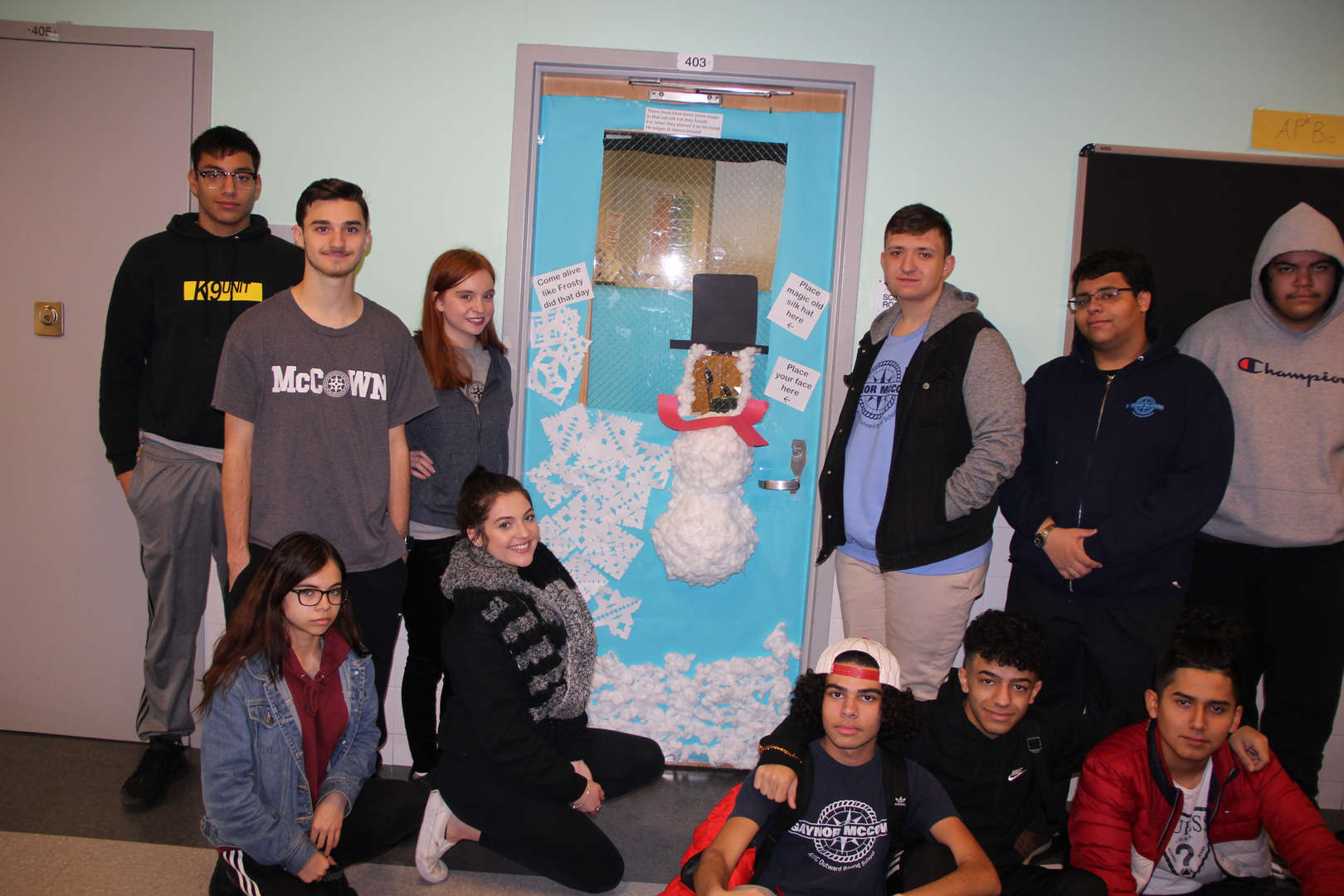 Group of students pose in front of snowman door decor