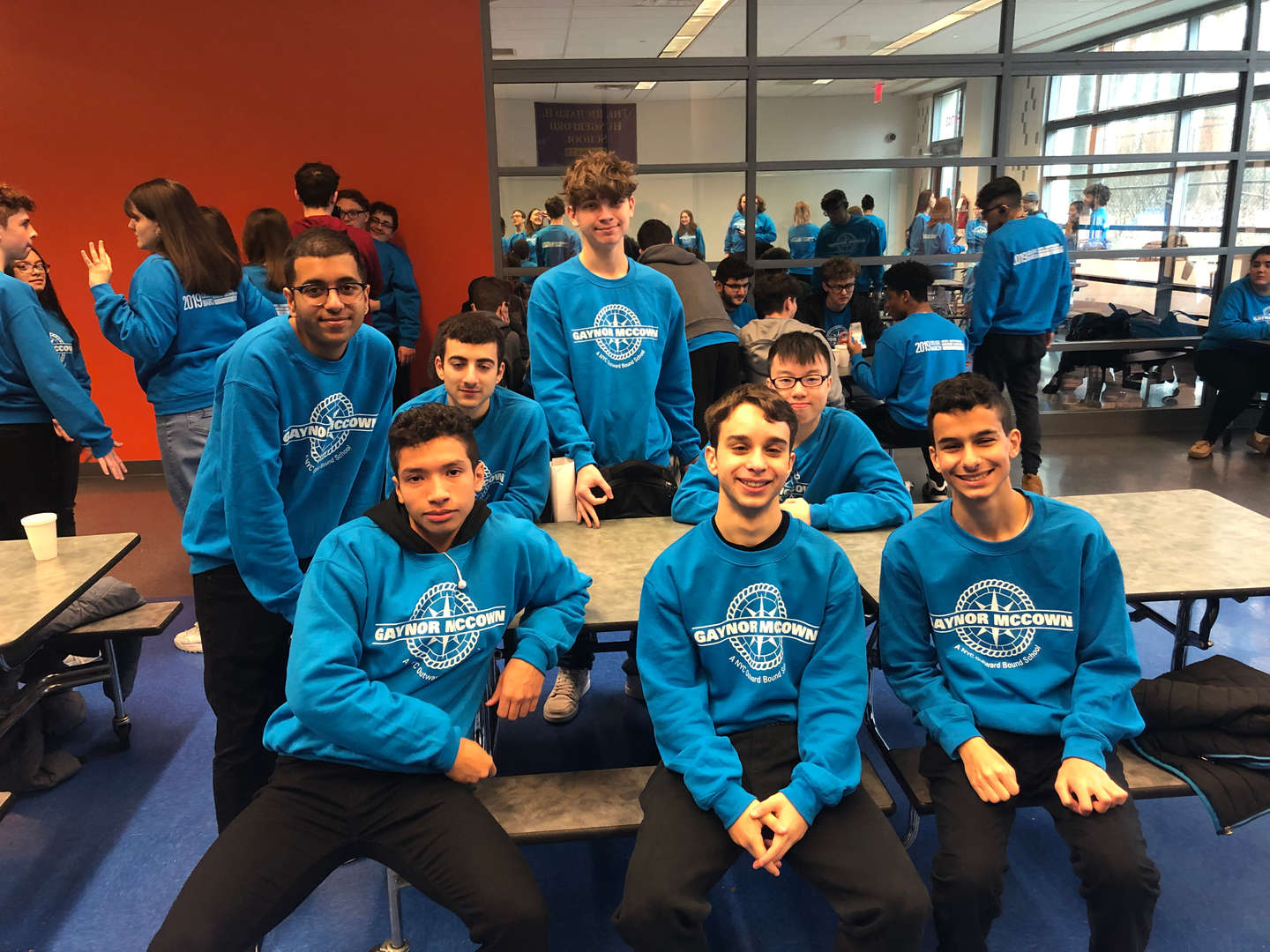 Group of boys sitting at table wearing blue Gaynor McCown sweatshirts