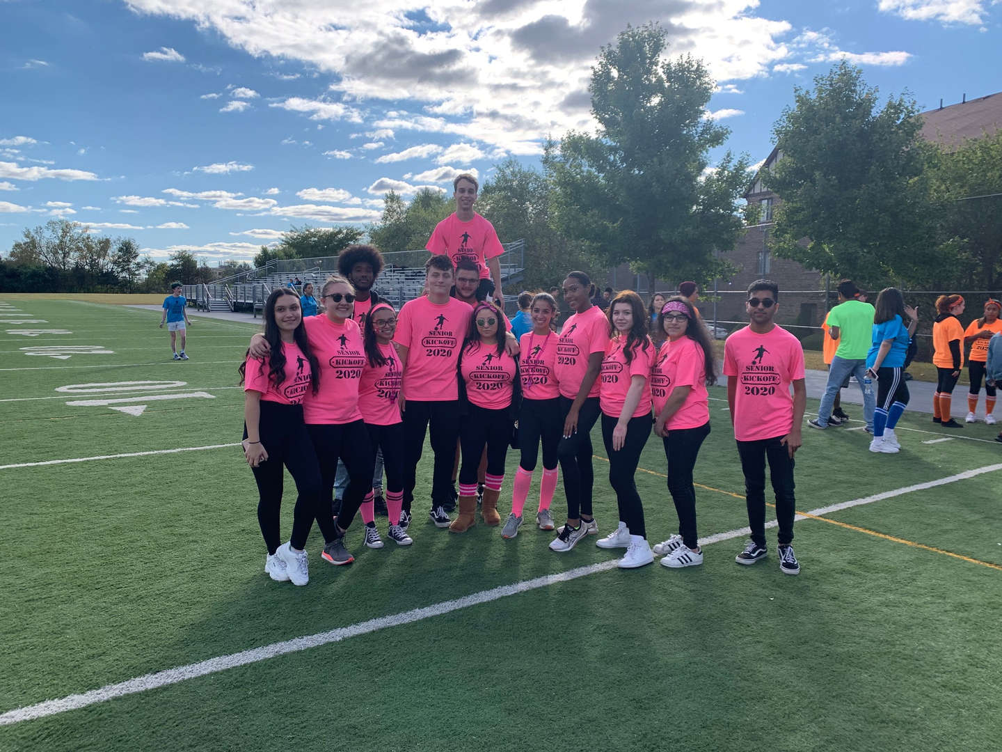 Group of students pose on football field during Senior Kickoff