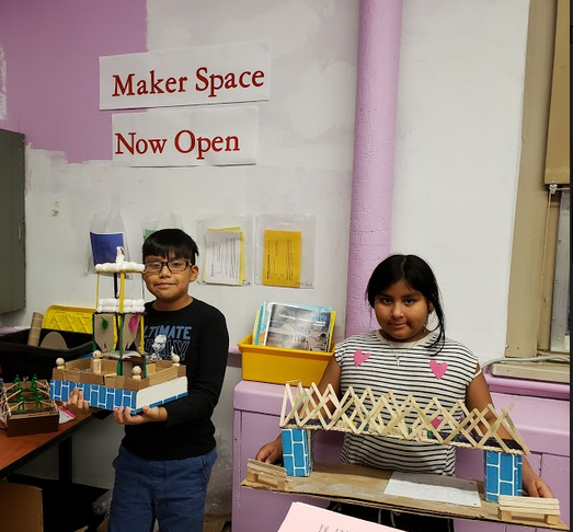 Two students show off their Maker space projects, a tower and a bridge.