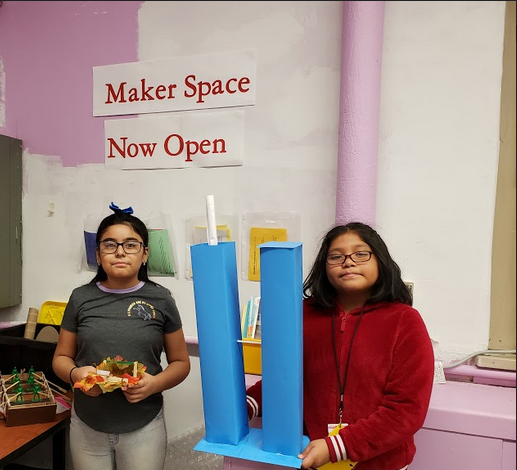Two students showing off their maker projects, a Catapult and  Twin Towers
