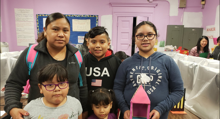 Families pose for a picture at the Maker Space Showcase