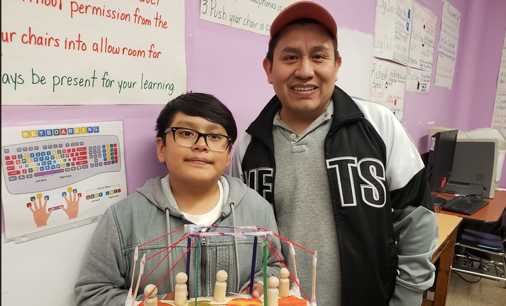 A Dad and his son pose for a Maker Space Showcase family picture