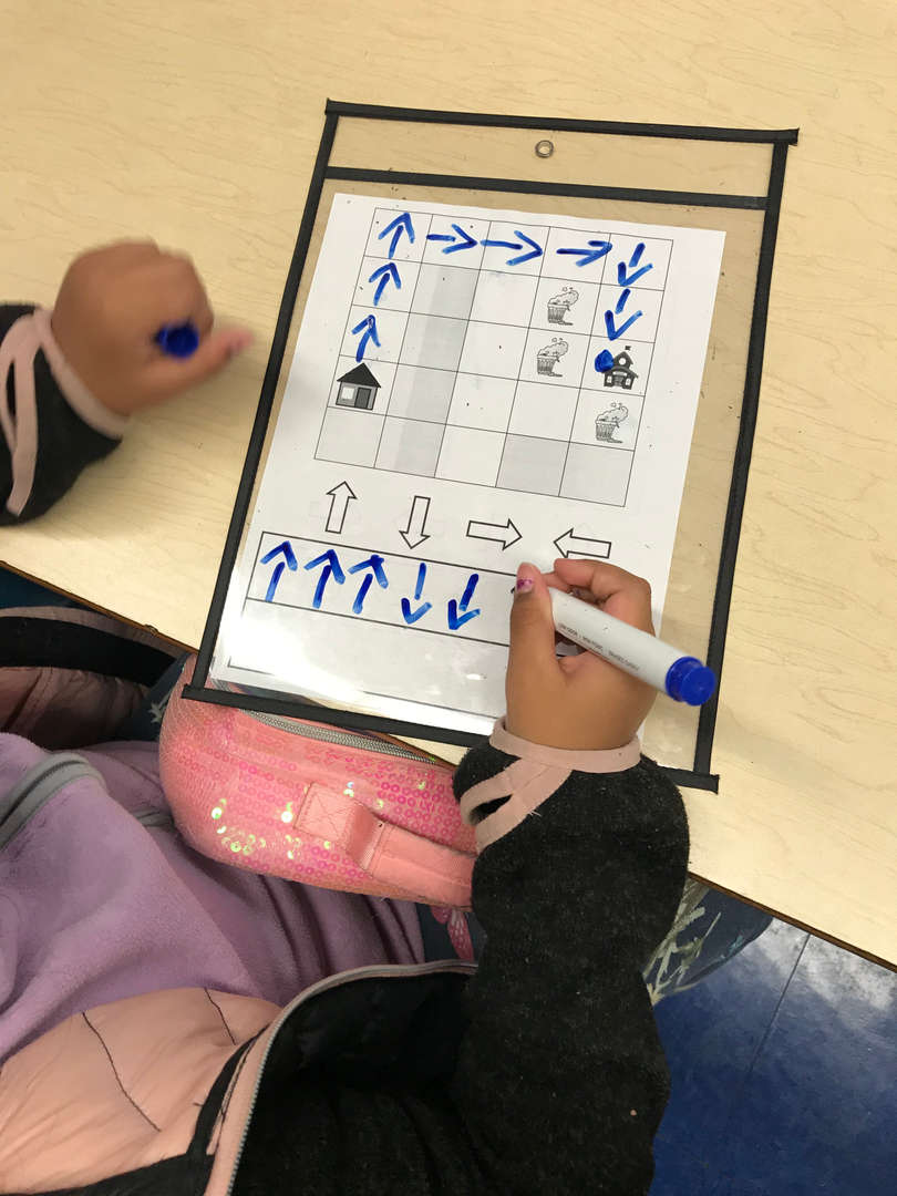 A student traces over directional arrows.