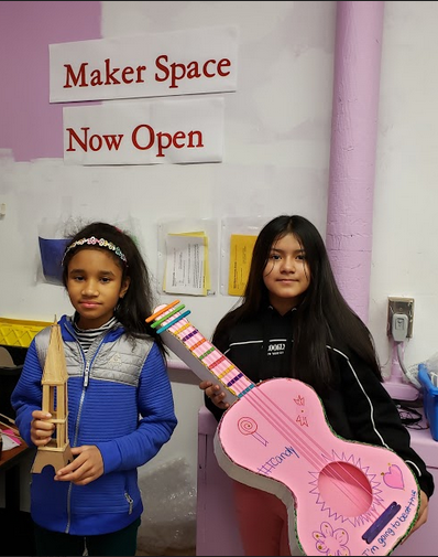 Two students share their finished Maker space projects, a Tower and a Guitar.
