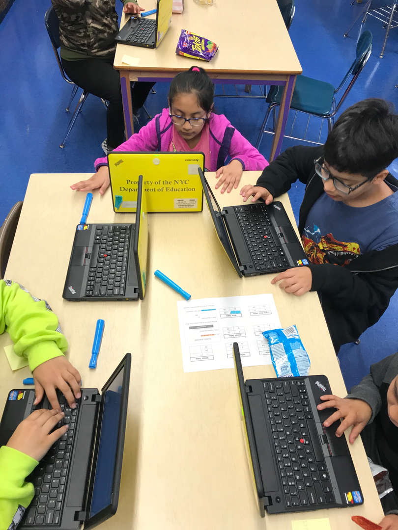 Five students work on programming on their laptops.
