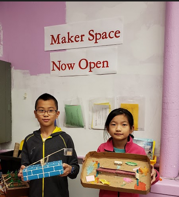 Two students share their finished maker space projects. A catapult and a bridge.