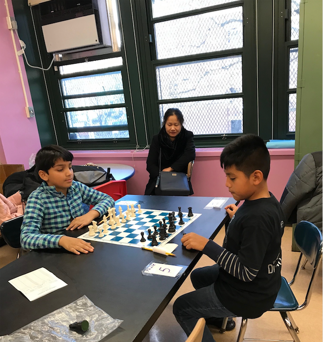 Two students focus on their chess match.