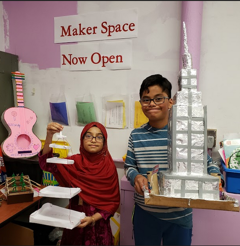 Two students sharing their Maker Space Towers they built.