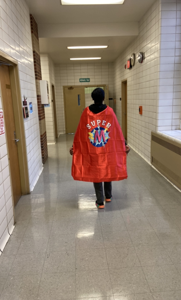 Ms Mitchell in a superhero cape back view