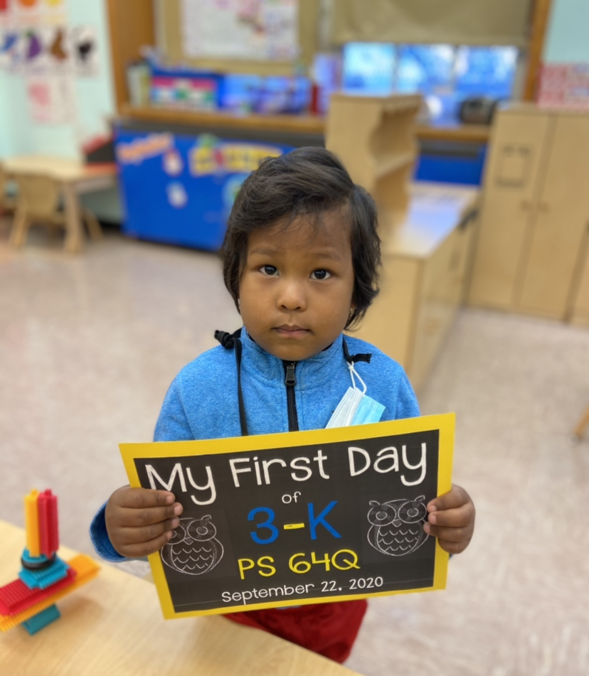 3-K student with a sign on his first day of school no mask