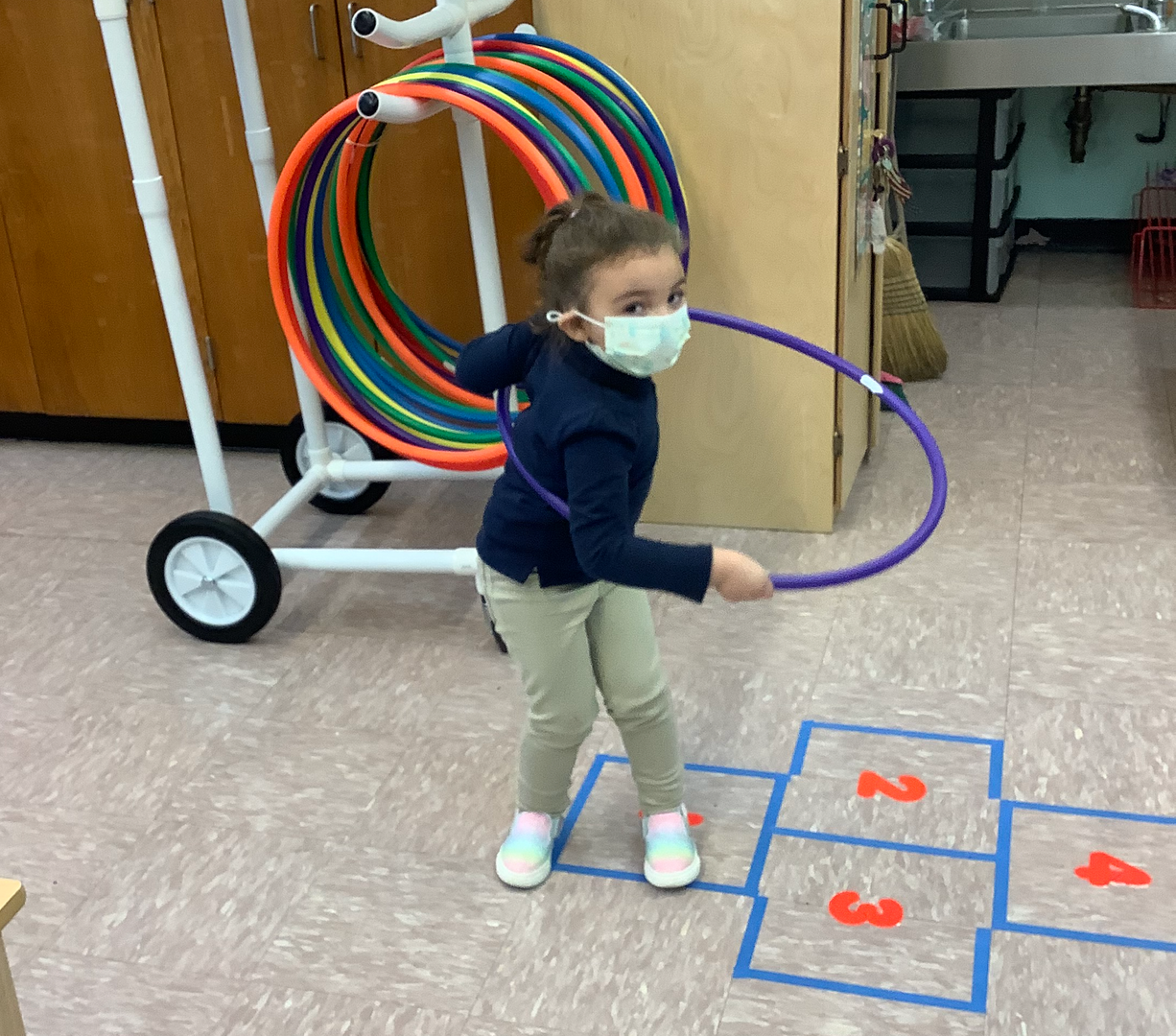 a student in a mask with a hula hoop