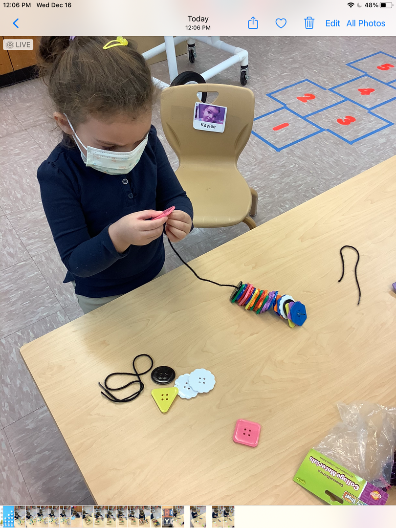 PreK students practice patterns with buttons on a string