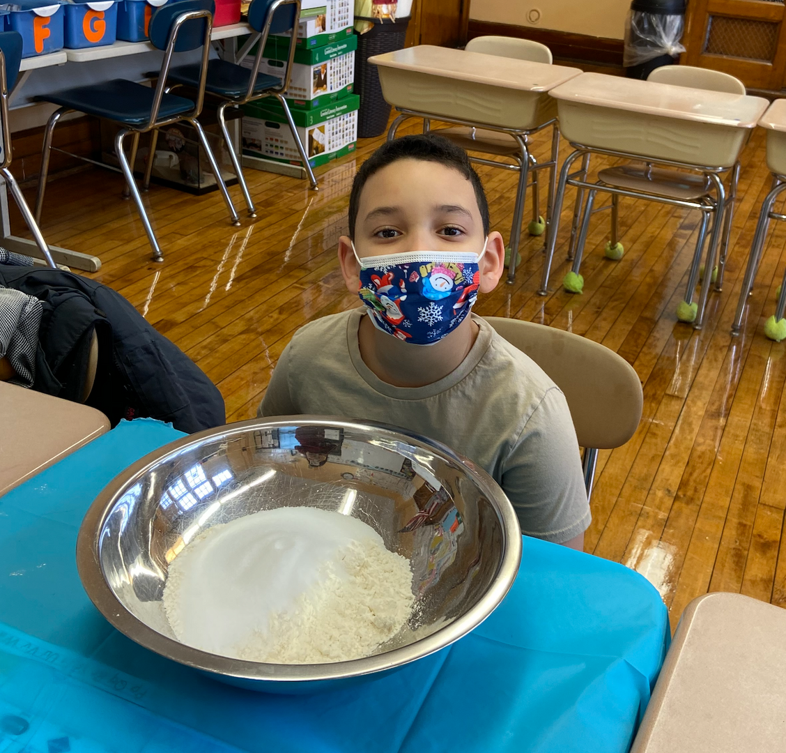 Ms. Scopo's student with a bowl for a science experiment
