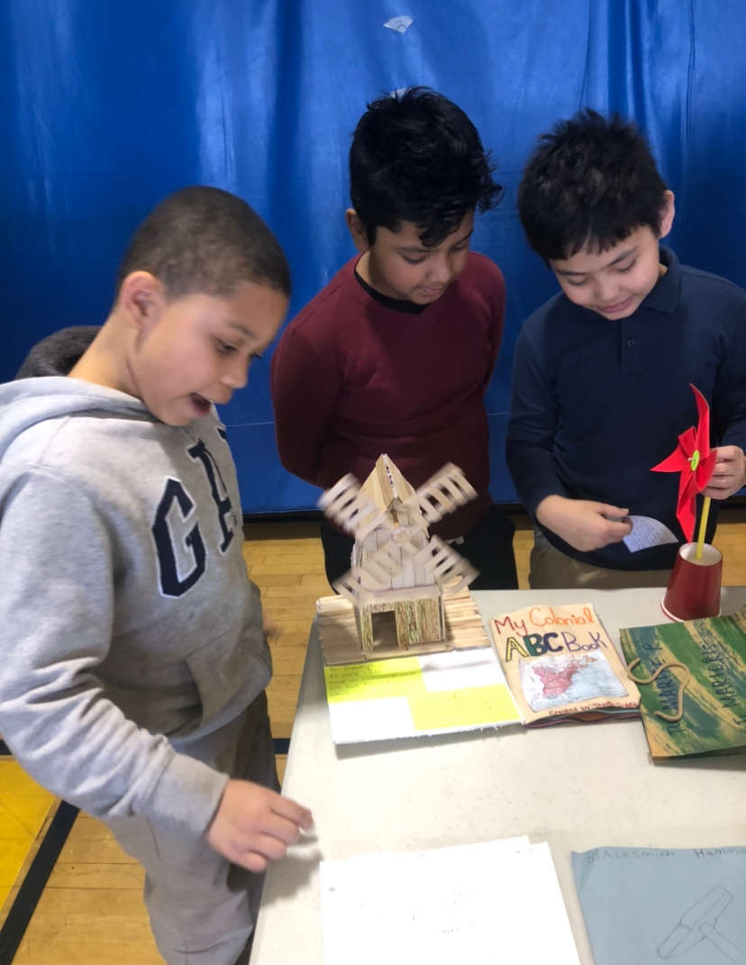 students looking at a windmill model