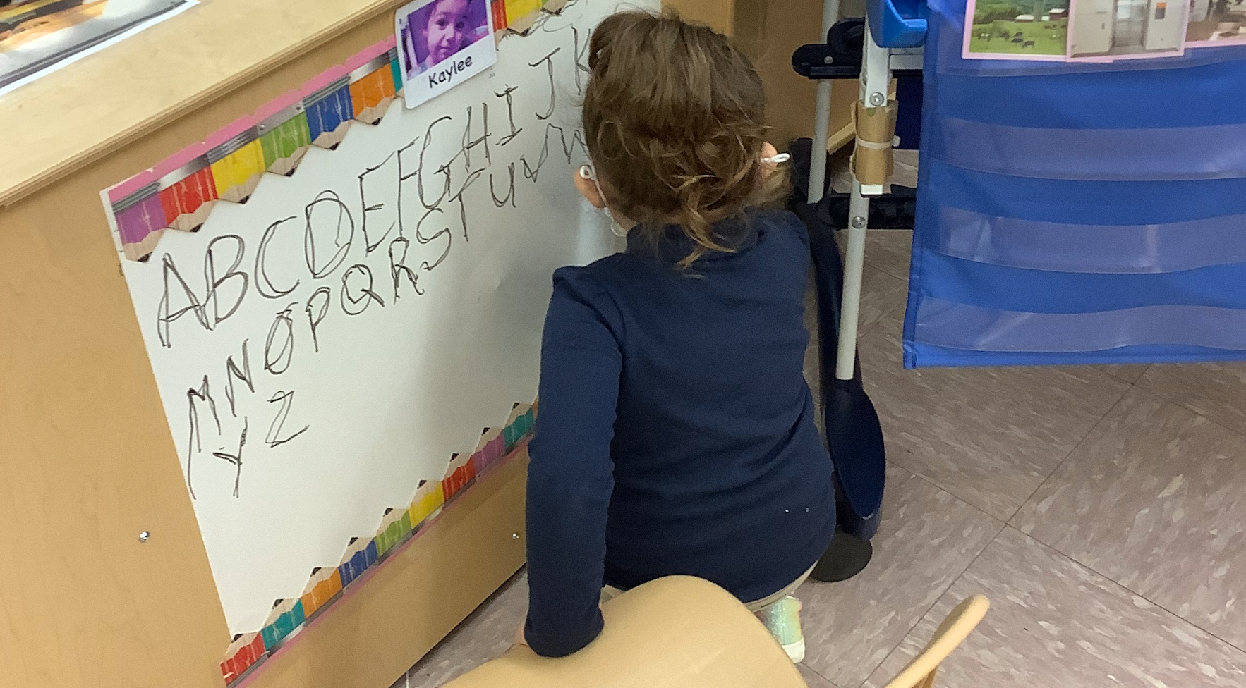 a student writing the alphabet on a poster