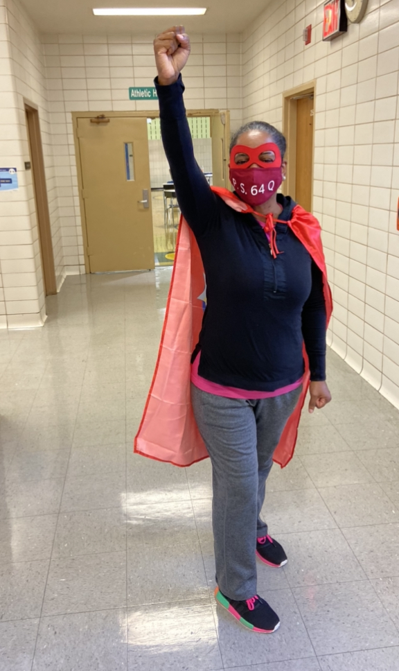 Ms Mitchell in a superhero cape