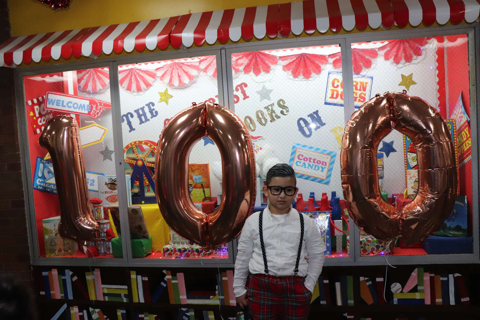 A student dressed like he is 100 in front of the number 100 balloons.